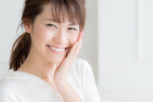 敏感肌に手を当てて微笑む女性